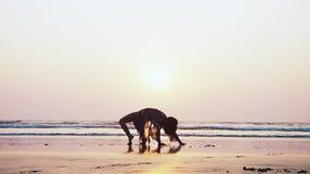 Σκιαγραφία της νέας gymnast γυναίκας που κάνει την ακροβατική τούμπα στην αμμώδη παραλία απόθεμα βίντεο