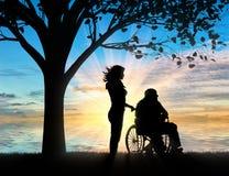 Σκιαγραφία της νοσοκόμας που φροντίζει για ένα με ειδικές ανάγκες άτομο σε μια αναπηρική καρέκλα που στηρίζεται κάτω από ένα δέντ Στοκ Φωτογραφία