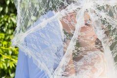Σκιαγραφία της νύφης και του νεόνυμφου πίσω από parasol δαντελλών Στοκ εικόνα με δικαίωμα ελεύθερης χρήσης