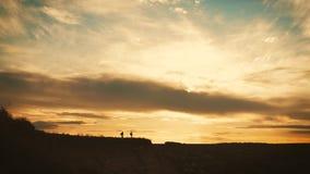 Σκιαγραφία της ομάδας στην αιχμή του βουνού Αθλητισμός και ενεργός ζωή του ατόμου και του κοριτσιού ανθρώπων Βοήθεια ζευγών ομαδι φιλμ μικρού μήκους