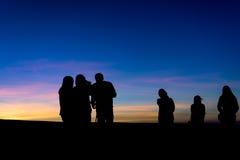 Σκιαγραφία της ομάδας ανθρώπων στην ανατολή στοκ εικόνες