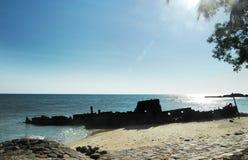 Σκιαγραφία της παλαιάς προσαραγμένης εγκαταλειμμένης συνεδρίασης ναυαγίου στην ακτή της παραλίας Στοκ Φωτογραφία