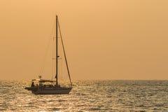Σκιαγραφία της πλέοντας βάρκας γιοτ που επιπλέει πέρα από την καθορισμένη θάλασσα ουρανού ήλιων, Στοκ φωτογραφία με δικαίωμα ελεύθερης χρήσης