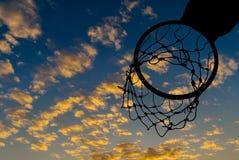 Σκιαγραφία της στεφάνης καλαθοσφαίρισης με το δραματικό ουρανό Στοκ Εικόνα