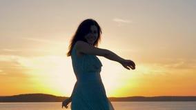 Σκιαγραφία της όμορφης γυναίκας που χορεύει και που θέτει στη κάμερα στο υπόβαθρο του ηλιοβασιλέματος απόθεμα βίντεο