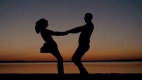 Σκιαγραφία του άνδρα και της γυναίκας στο ηλιοβασίλεμα με τα χέρια και να περιβάλει εκμετάλλευσης παραλιών απόθεμα βίντεο