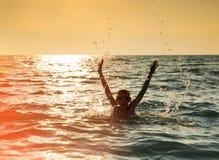 Σκιαγραφία του άλματος αγοριών στη θάλασσα Στοκ Φωτογραφία