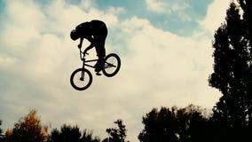 Σκιαγραφία του άλτη, που εκτελεί το ποδήλατο βουνών BMX απόθεμα βίντεο