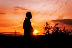 Σκιαγραφία του λίπους ατόμων που στέκεται στο ηλιοβασίλεμα Στοκ Εικόνες