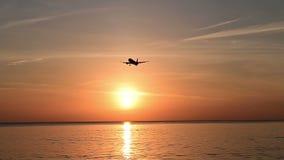 Σκιαγραφία του αεροπλάνου που πετά σε αργή κίνηση για την προσγείωση στον αερολιμένα με την ωκεάνια άποψη απόθεμα βίντεο