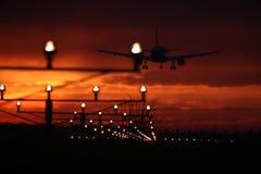 Σκιαγραφία του αεροπλάνου που προσγειώνεται, φω'τα διαδρόμων, πορτοκαλιά επίδραση στοκ εικόνες