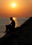 Συνεδρίαση ατόμων σε έναν βράχο και απόλαυση του ηλιοβασιλέματος Στοκ Εικόνες