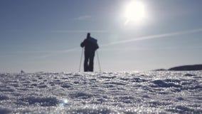 Σκιαγραφία του ατόμου με ένα σακίδιο πλάτης που περπατά σε ένα χειμερινό τοπίο στα πλέγματα σχήματος ρακέτας Πραγματοποιώντας οδο φιλμ μικρού μήκους