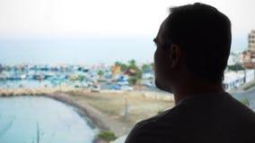 Σκιαγραφία του ατόμου που απολαμβάνει τη θέα θάλασσας από το πεζούλι Αρσενικός ταξιδιώτης που εξετάζει τη μαρίνα από το μπαλκόνι φιλμ μικρού μήκους