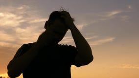 Σκιαγραφία του ατόμου που γρατσουνίζει το κεφάλι του ενάντια στο ηλιοβασίλεμα απόθεμα βίντεο