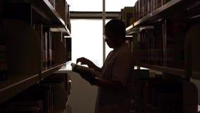 Σκιαγραφία του ατόμου που διαβάζει ένα βιβλίο στη βιβλιοθήκη απόθεμα βίντεο