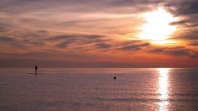 Σκιαγραφία του ατόμου στον κάνοντας σερφ πίνακα εν πλω στο ηλιοβασίλεμα Θάλασσα ηλιοβασιλέματος Αντανάκλαση ήλιων φιλμ μικρού μήκους