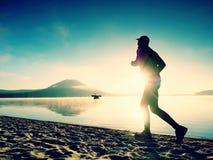 Σκιαγραφία του ενεργού αθλητή που τρέχει στην παραλία λιμνών στην ανατολή Υγιής τρόπος ζωής Στοκ Εικόνες
