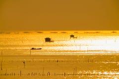 Σκιαγραφία του εξοχικού σπιτιού ψαράδων και ένας λεμβούχος στον ποταμό στη χρυσή ηλιοφάνεια Στοκ εικόνες με δικαίωμα ελεύθερης χρήσης