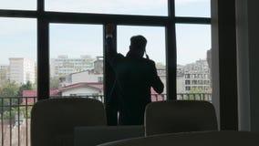 Σκιαγραφία του επιχειρηματία που μιλά στο τηλέφωνο κοντά στο παράθυρο απόθεμα βίντεο