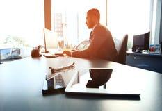 Σκιαγραφία του επιχειρηματία που χρησιμοποιεί το lap-top Στοκ Εικόνα