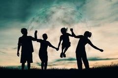 Σκιαγραφία του ευτυχούς οικογενειακού παιχνιδιού στον ουρανό με το φεγγάρι Στοκ Εικόνα