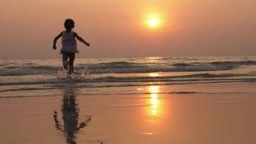 Σκιαγραφία του ευτυχούς παιδιού που τρέχει στη θάλασσα στο όμορφο φως ηλιοβασιλέματος φιλμ μικρού μήκους