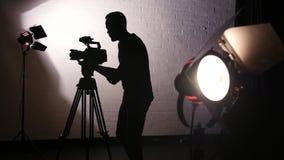 Σκιαγραφία του καμεραμάν που λειτουργεί πίσω από τις σκηνές στο κινηματογραφικό στούντιο απόθεμα βίντεο
