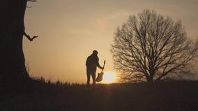 Σκιαγραφία του κιθαρίστα στο ηλιοβασίλεμα σε αργή κίνηση κυματισμός της κιθάρας και του χεριού του φιλμ μικρού μήκους
