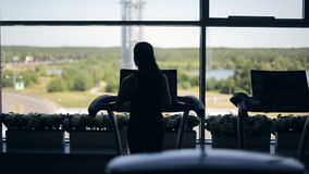 Σκιαγραφία του κοριτσιού που τρέχει treadmill και που εξετάζει το μεγάλο παράθυρο Το αριστερό στο δικαίωμα μετακινείται τον πυροβ απόθεμα βίντεο