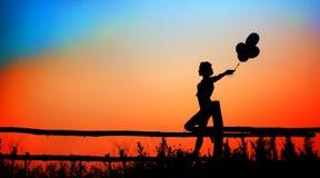 Σκιαγραφία του κοριτσιού στο ηλιοβασίλεμα Στοκ φωτογραφία με δικαίωμα ελεύθερης χρήσης