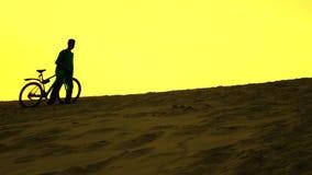Σκιαγραφία του μόνου ποδηλάτη που περπατά με το ποδήλατό του κατά μήκος του αμμόλοφου άμμου, κίτρινα χρώματα ηλιοβασιλέματος Στοκ Φωτογραφίες