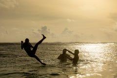 Σκιαγραφία του νέου άλματος γυναικών από τον ωκεανό Στοκ φωτογραφία με δικαίωμα ελεύθερης χρήσης