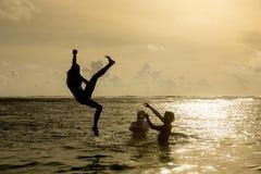Σκιαγραφία του νέου άλματος γυναικών από τον ωκεανό Στοκ Φωτογραφία