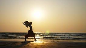 Σκιαγραφία του νέου κοριτσιού με τα φτερά αγγέλου που χορεύουν στο ηλιοβασίλεμα σε σε αργή κίνηση απόθεμα βίντεο