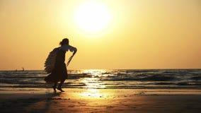 Σκιαγραφία του νέου κοριτσιού με τα φτερά που χορεύουν στο ηλιοβασίλεμα σε σε αργή κίνηση φιλμ μικρού μήκους