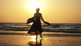 Σκιαγραφία του νέου κοριτσιού με τα φτερά που χορεύουν στο ηλιοβασίλεμα σε σε αργή κίνηση