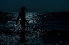 Σκιαγραφία του νέου, λεπτού, προκλητικού περπατήματος γυναικών στη θάλασσα κάτω από το σεληνόφωτο Στοκ Εικόνα