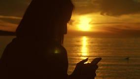Σκιαγραφία του νέου τηλεφώνου χρήσης γυναικών τουριστών κατά τη διάρκεια του ηλιοβασιλέματος στην ωκεάνια παραλία Πάντα συνδεμένο φιλμ μικρού μήκους