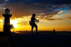 Σκιαγραφία του νεαρού άνδρα που αλιεύει κοντά στην παραλία Στοκ Φωτογραφία