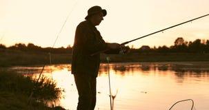 Σκιαγραφία του παλαιού ψαρά στο υπόβαθρο ενός όμορφου ηλιοβασιλέματος φιλμ μικρού μήκους