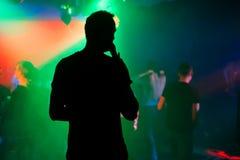 Σκιαγραφία του παρουσιαστή με ένα μικρόφωνο στη σκηνή του νυχτερινού κέντρου διασκέδασης στη συναυλία στοκ φωτογραφία