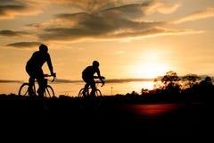 Σκιαγραφία του ποδηλάτου γύρου ποδηλατών στο υπόβαθρο ηλιοβασιλέματος Στοκ Φωτογραφίες
