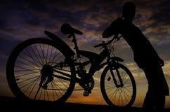 Σκιαγραφία του ποδηλάτη με τον ουρανό λυκόφατος Στοκ εικόνες με δικαίωμα ελεύθερης χρήσης