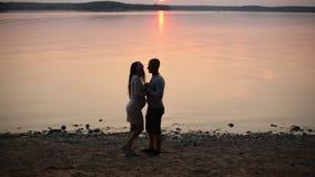 Σκιαγραφία του ρομαντικού ζεύγους που περπατά στην ακτή λιμνών και που φιλά στο ηλιοβασίλεμα φιλμ μικρού μήκους
