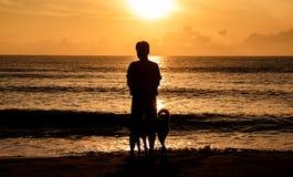Σκιαγραφία του σκυλιού και του ιδιοκτήτη που περπατούν στην παραλία το πρωί και την όμορφη ανατολή στην παραλία Krut απαγόρευσης, στοκ εικόνα με δικαίωμα ελεύθερης χρήσης