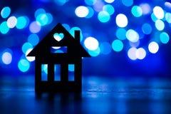 Σκιαγραφία του σπιτιού με την τρύπα με μορφή καρδιάς στην μπλε ΤΣΕ bokeh Στοκ φωτογραφία με δικαίωμα ελεύθερης χρήσης