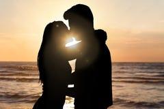 Σκιαγραφία του φιλήματος ζευγών στην παραλία κατά τη διάρκεια του ηλιοβασιλέματος Στοκ εικόνα με δικαίωμα ελεύθερης χρήσης