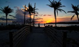 Σκιαγραφία του φωτογράφου και beachcomber της προσοχής ενός βαθιού πορτοκαλιού ηλιοβασιλέματος πέρα από τον ορίζοντα στην παραλία στοκ εικόνες