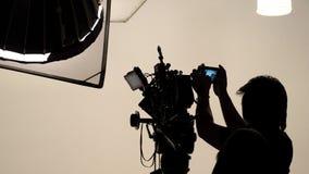 Σκιαγραφία του φωτογράφου που ελέγχει για τη κάμερα κινηματογράφων Στοκ φωτογραφία με δικαίωμα ελεύθερης χρήσης